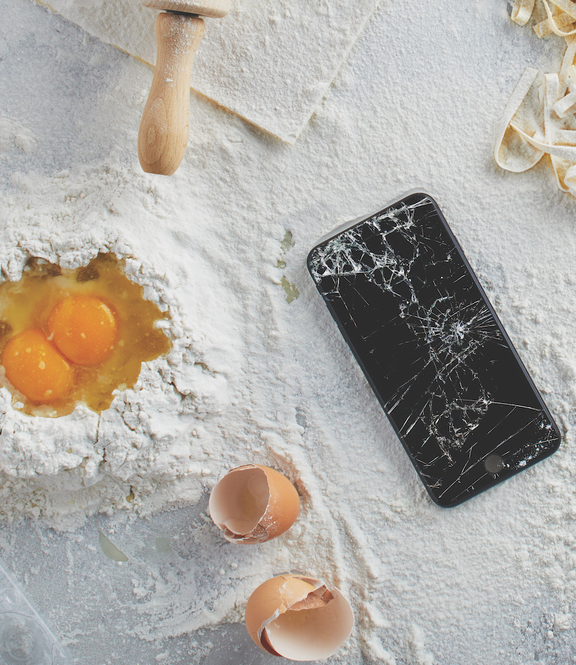 Phone on white table with flour and cracked eggs
