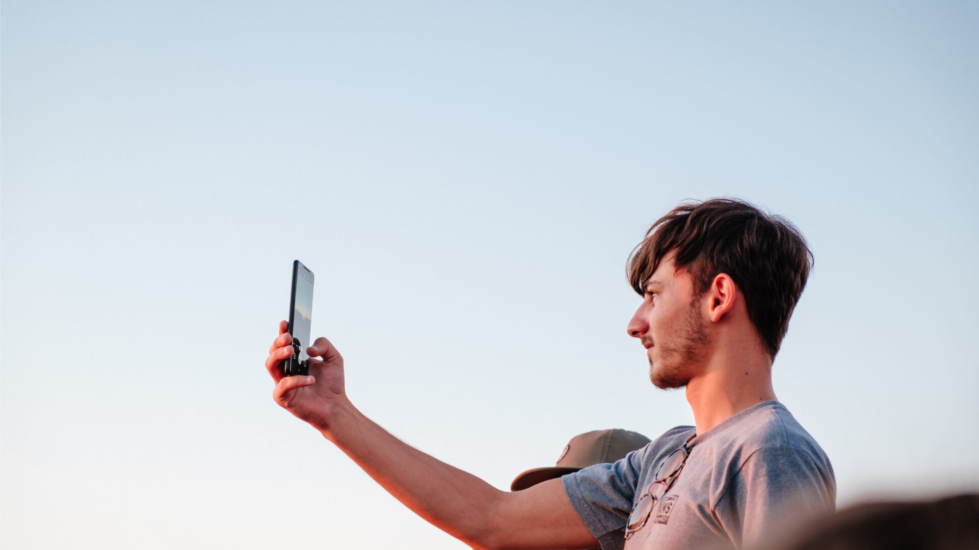 Man holding phone out and taking a photo of a sunset